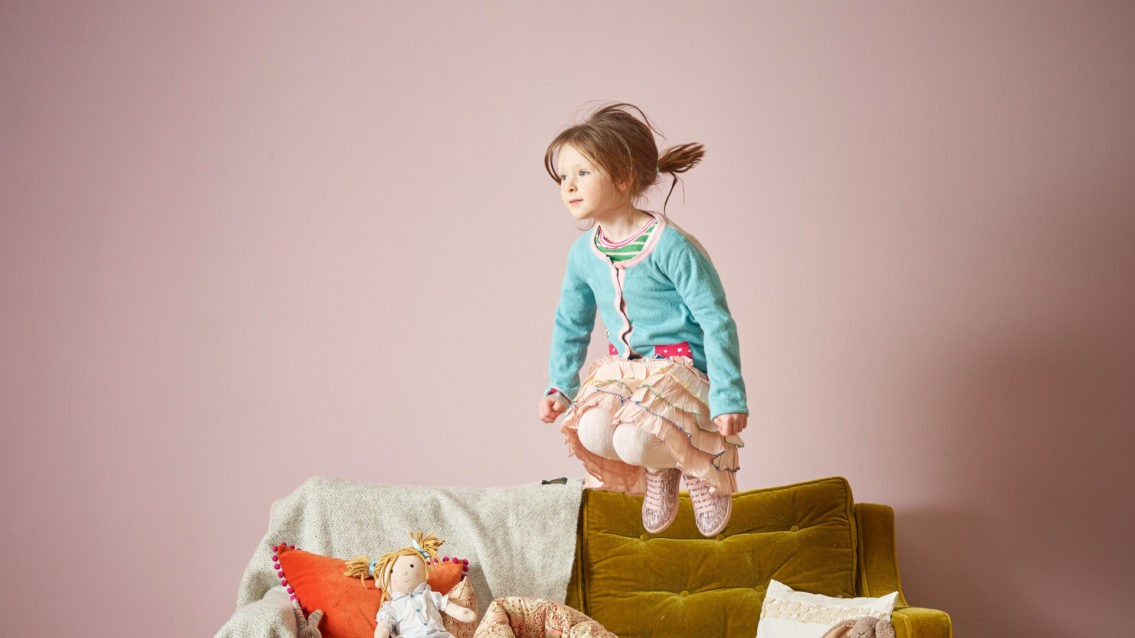 A child jumps on a sofa